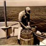 "Edgar Post filling bait bags with herring ""cuttings"" from a sardine factory."